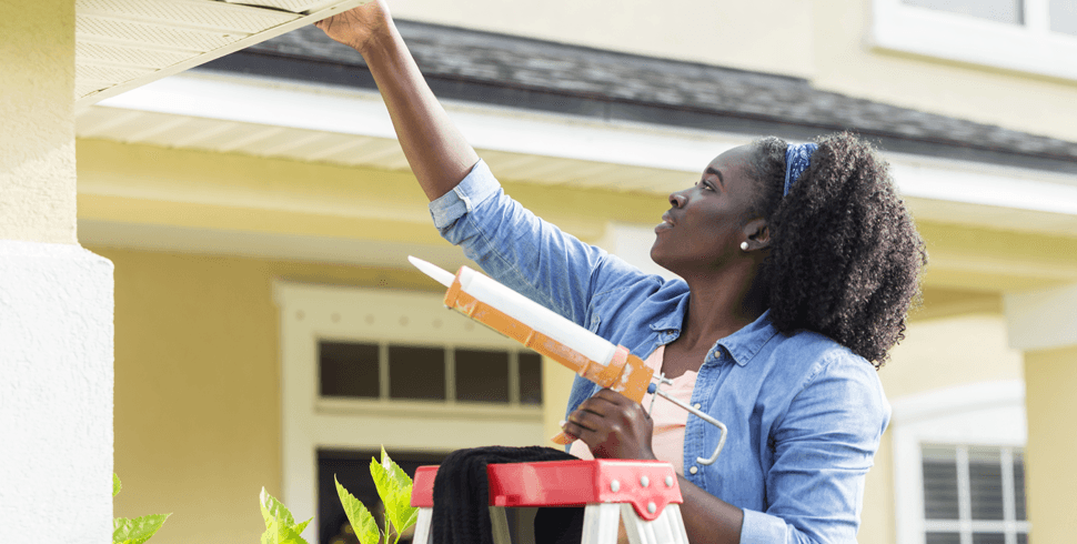 Woman fixing roof of home