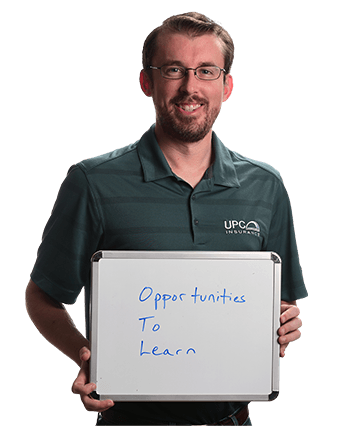 Lee Knepler holding a sign which reads 'Opportunities to Learn'